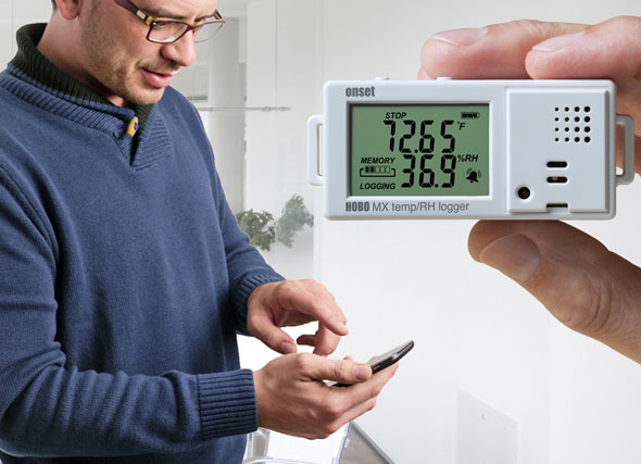Man checking an Onset Temperature/RH Data Logger on a mobile device with Bluetooth